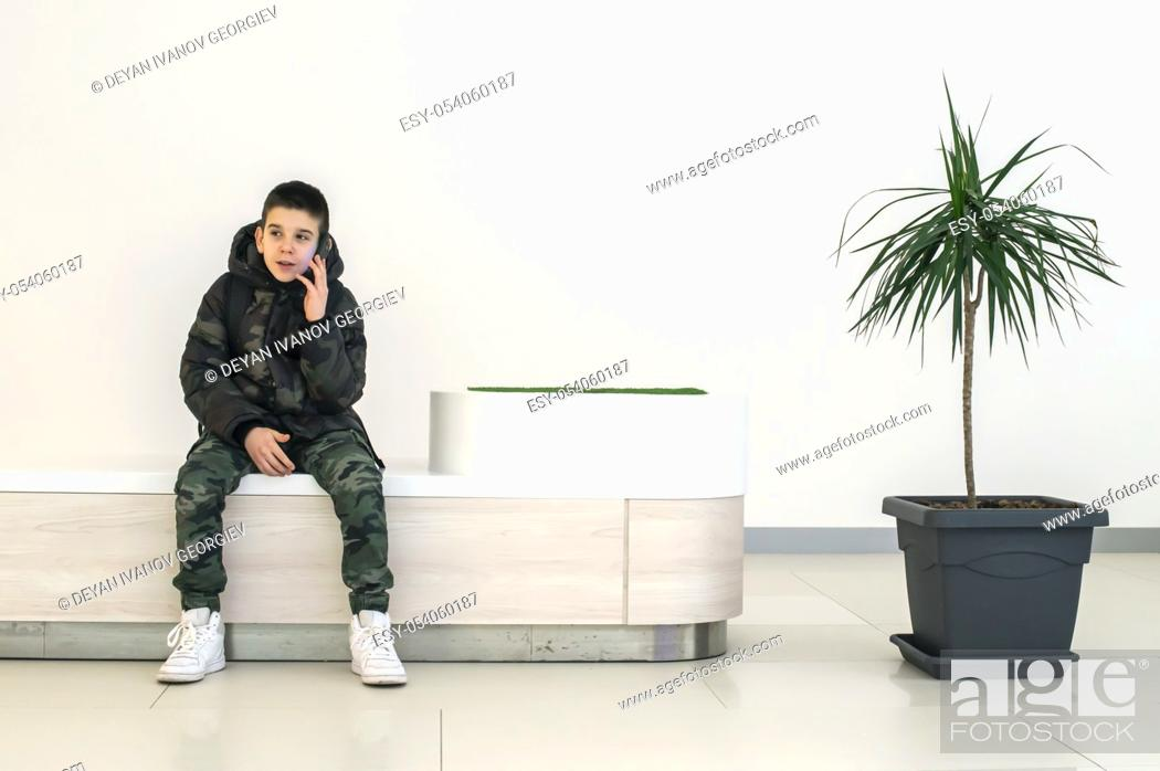 Stock Photo: Teenager talking on smartphone in modern commercial center. Bench and flower in a pot. Modern building interior. Technology and communication concept with child.