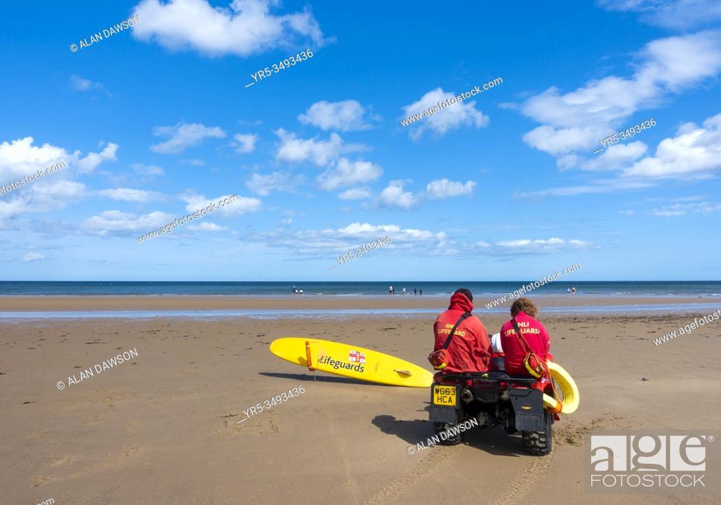 Stock Photo: Lifeguards sitting on quad bike at Saltburn by the sea, North Yorkshire, England. United Kingdom.