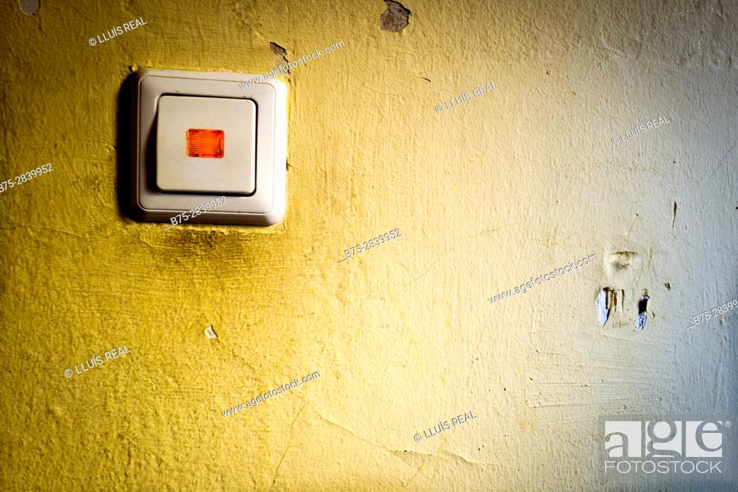 Stock Photo: Power switch with a red light on yellow wall in a residential building. Neukölln, Berlin, Germany.