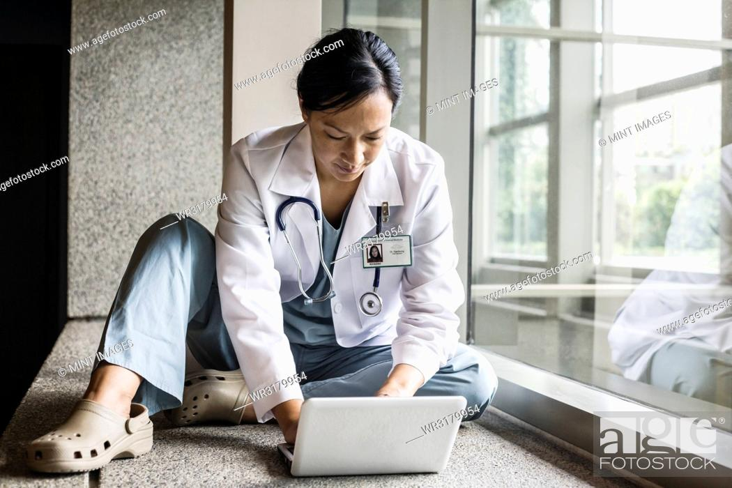 Stock Photo: Asian woman doctor working on a lap top in a hospital hallway.