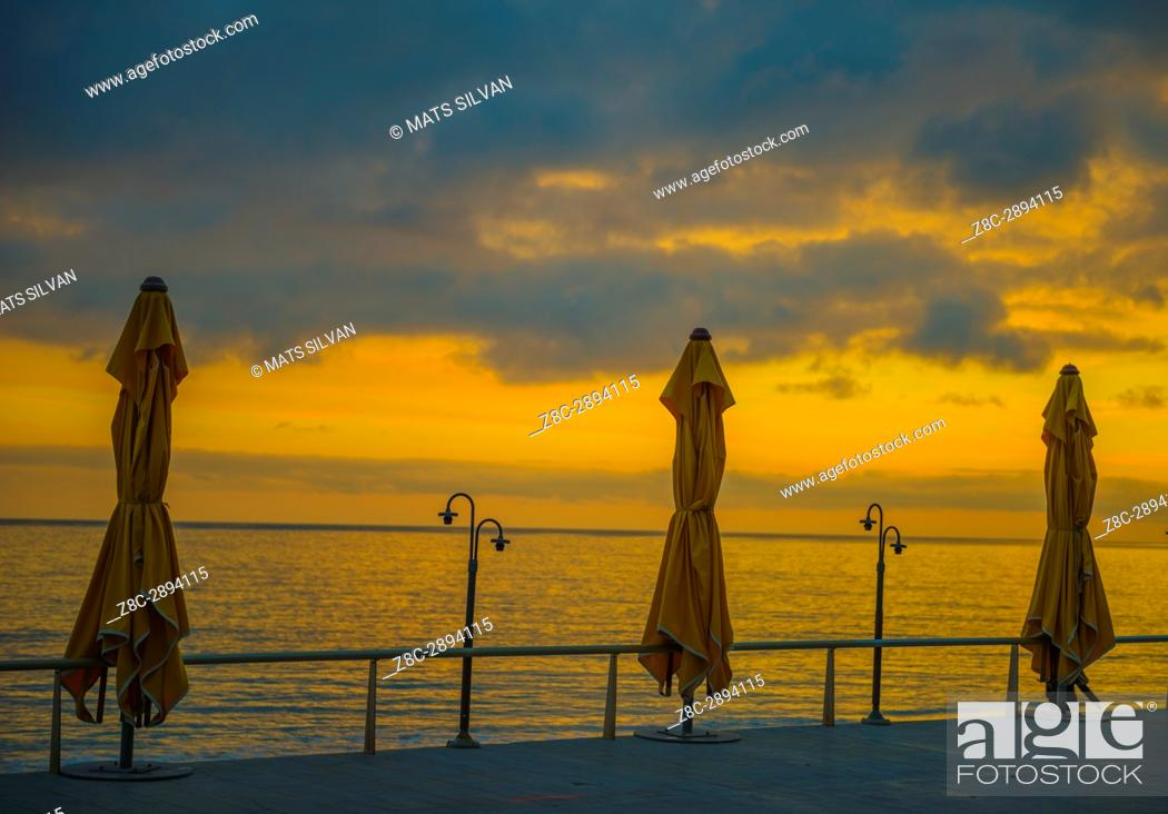 Stock Photo: Parasol on the Coastline to Mediterranean Sea in Sunset in Menton, Provence-Alpes-Côte d'Azur, France.