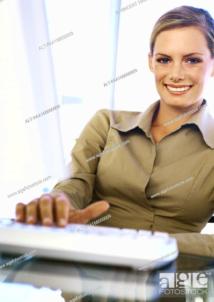 Stock Photo: Businesswoman with hand on keyboard, smiling, portrait.