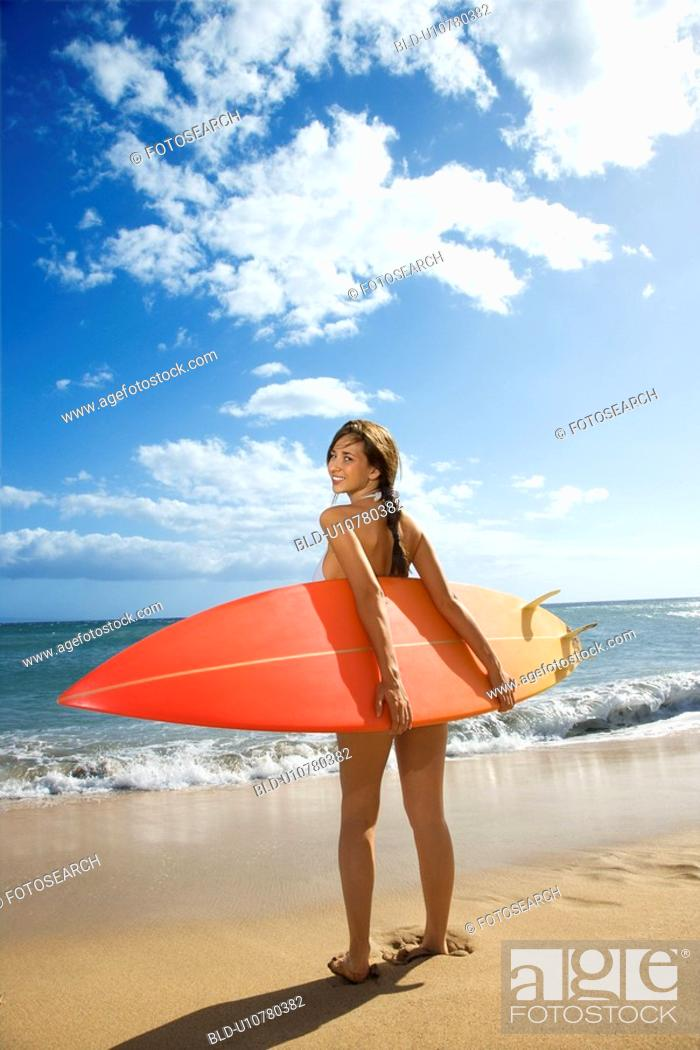 Stock Photo: Young pretty woman in bikini standing with surfboard at beach.