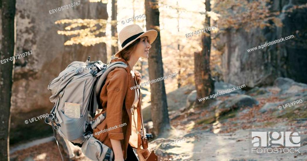 Stock Photo: Young traveler female in a broad-brimmed hat and backpack admires the forest, looks around close-up 4k.
