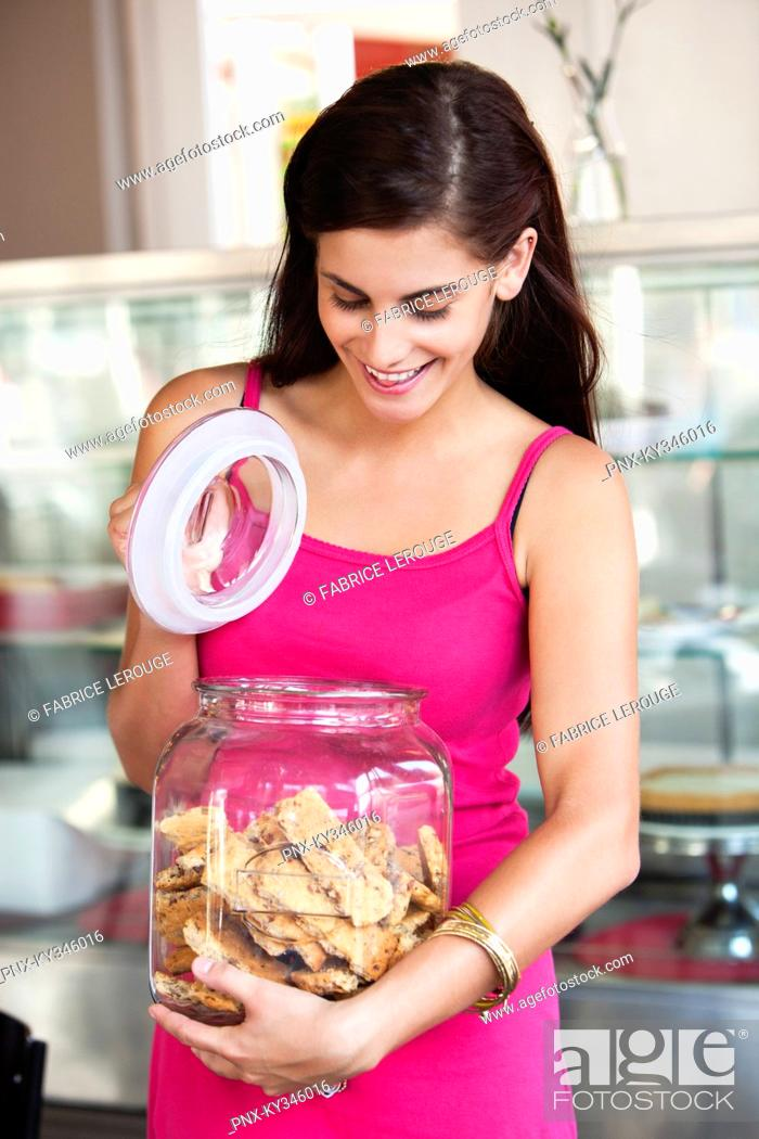 Stock Photo: Smiling woman opening a jar of cookies in a bakery.
