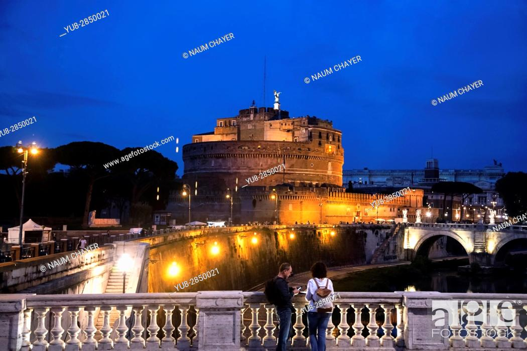 Stock Photo: Couple of tourist watching Castel Sant'Angelo from bridge at night, Rome, Italy, Europe.