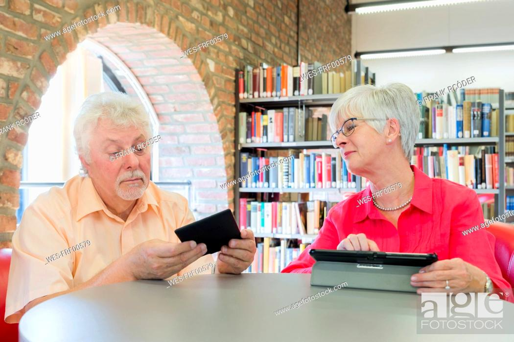 Stock Photo: Senior couple with tablet and e-book in a city library.