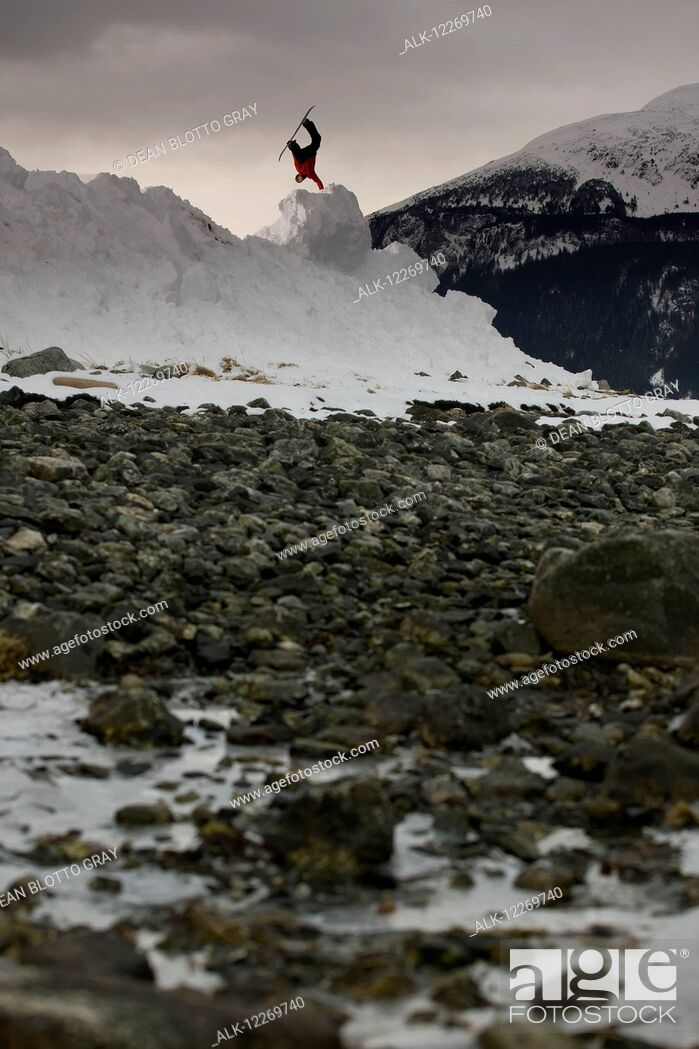 Imagen: Snowboarder makes a jump on a snow hill with rocks in the foreground, Haines, Southeast Alaska.