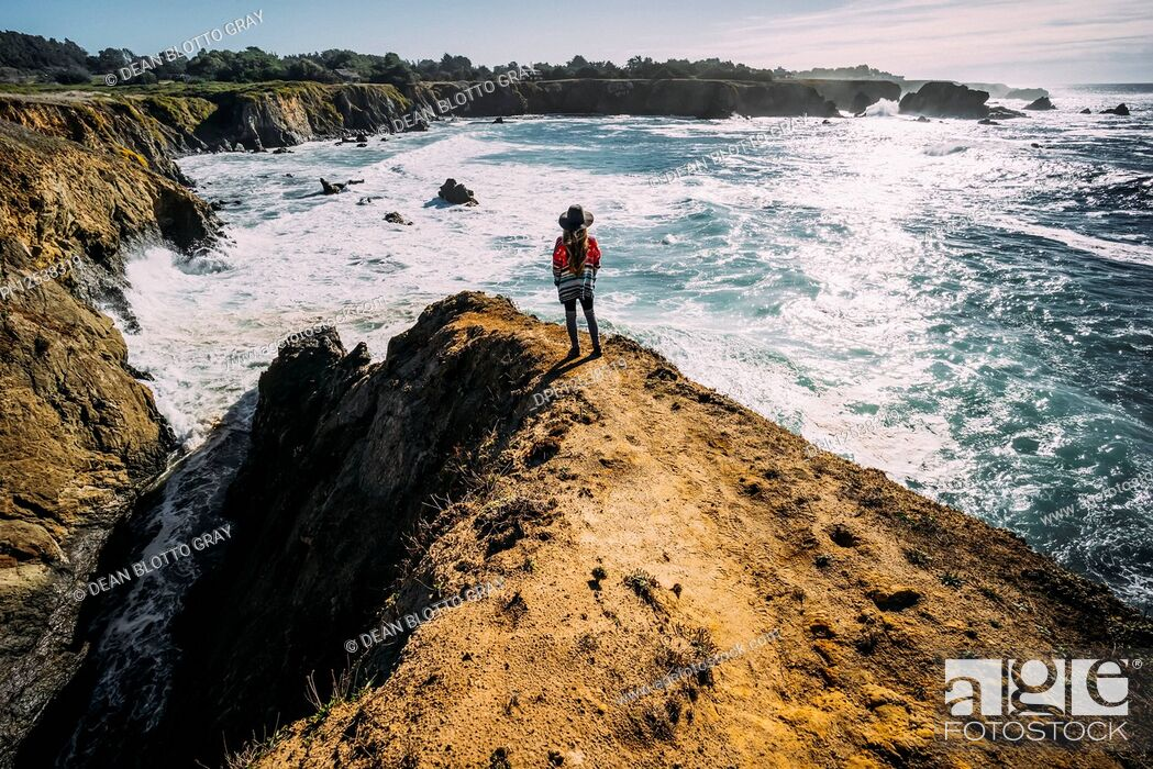 Stock Photo: A woman stands looking out along the Russian Gulch Headlands, Mendocino county; California, United States of America.