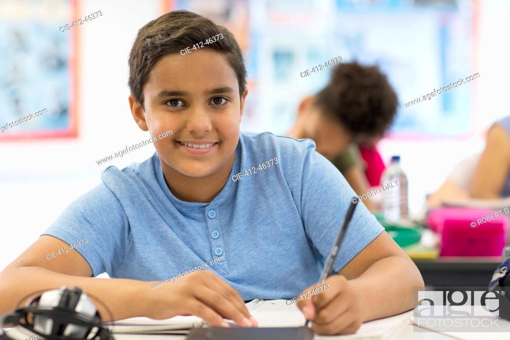 Stock Photo: Portrait confident junior high school boy student doing homework in classroom.
