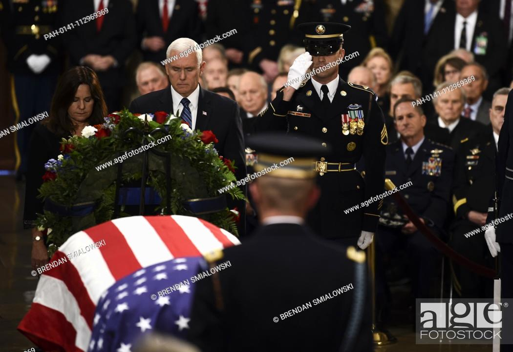 Stock Photo: US Vice President Mike Pence (2L) and Second Lady of the United States Karen Pence (L) pay their respects at the casket bearing the remains of former US.