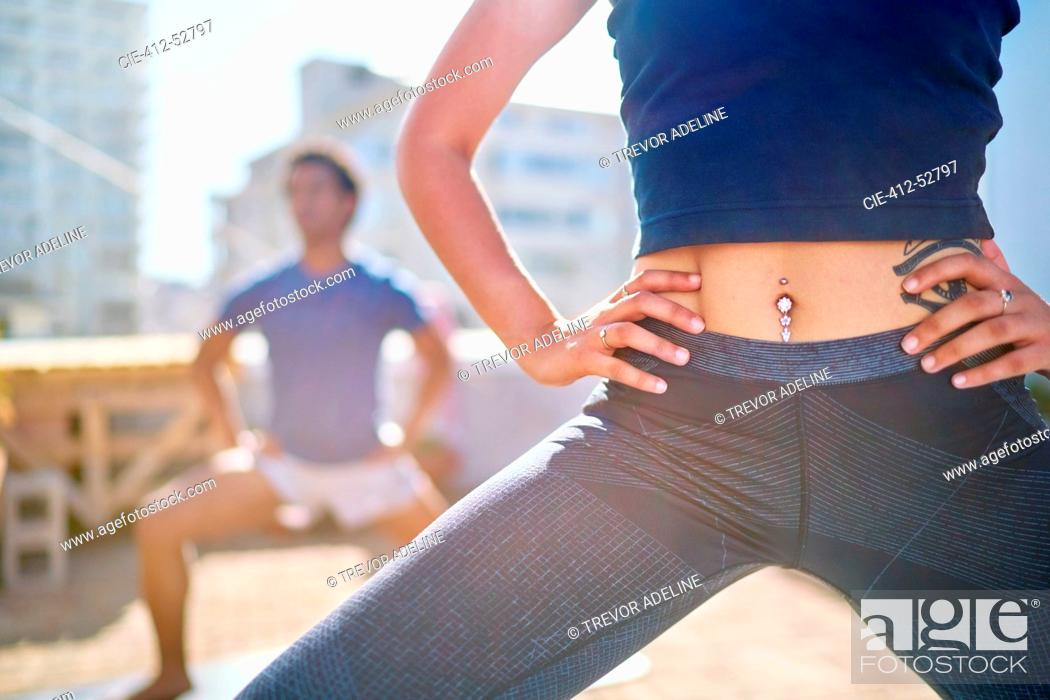 Stock Photo: Close up young woman with belly piercing practicing yoga on balcony.