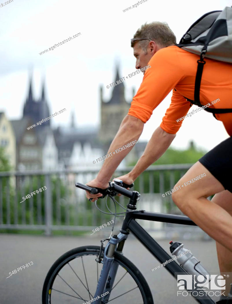 Stock Photo: Bicycle courier cycling across bridge, side view.