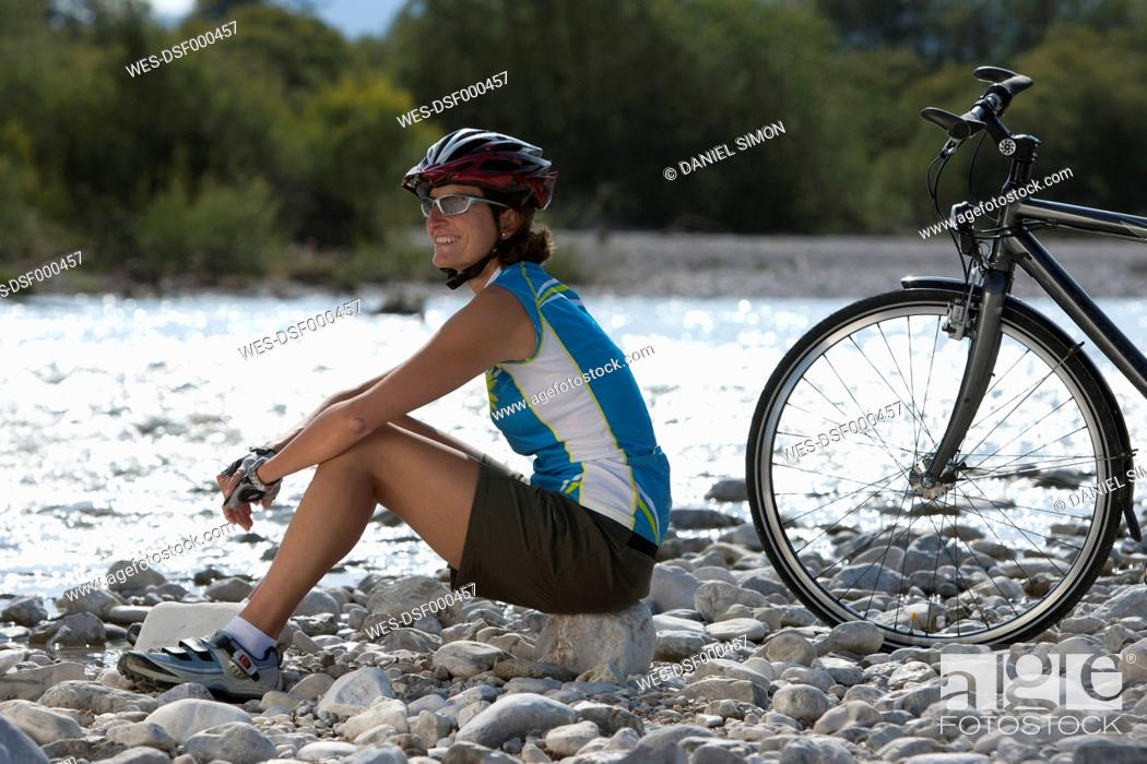 Stock Photo: Germany, Bavaria, Mid adult woman looking away, smiling.