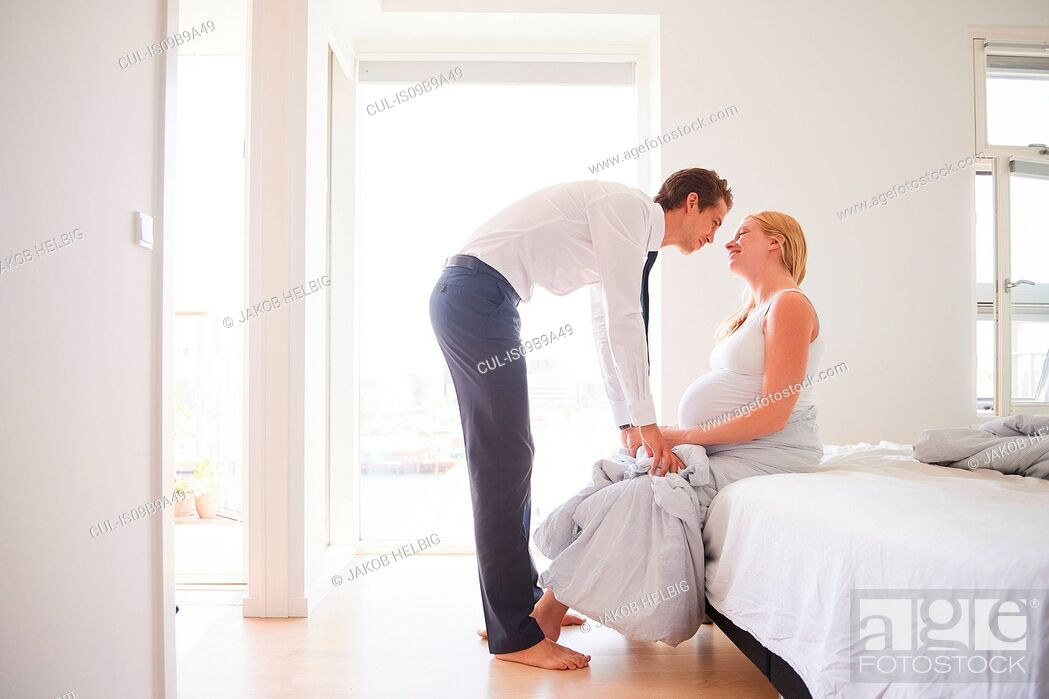 Stock Photo: Romantic pregnant couple face to face in bedroom.