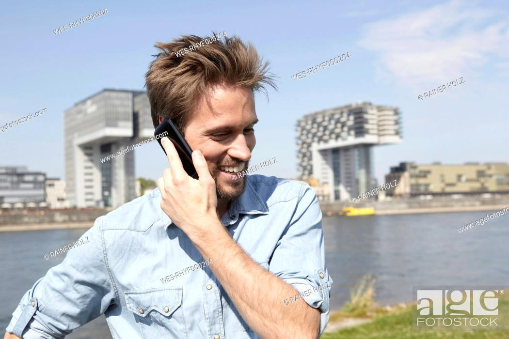 Stock Photo: Germany, Cologne, Mid adult man talking on cell phone.