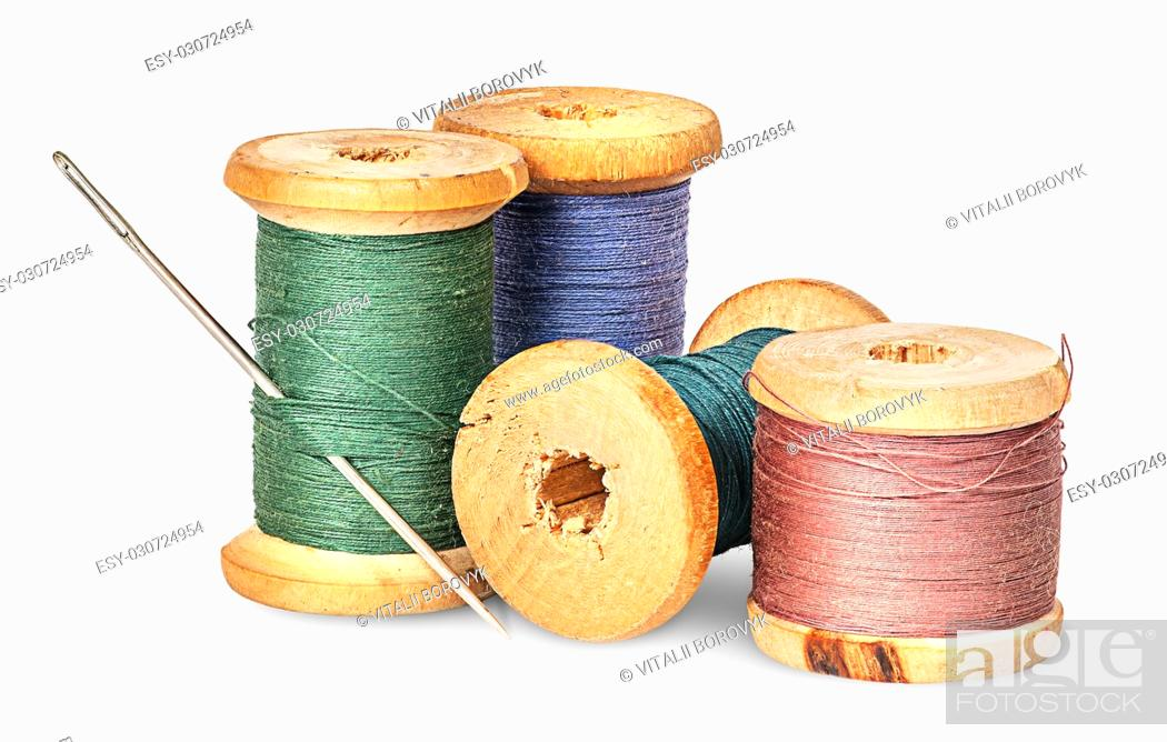 Stock Photo: Needle and multicolored thread on wooden spool isolated on white background.