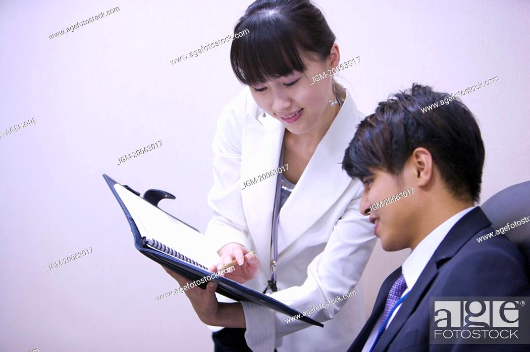 Stock Photo: Young woman showing document folder to young man with smile.
