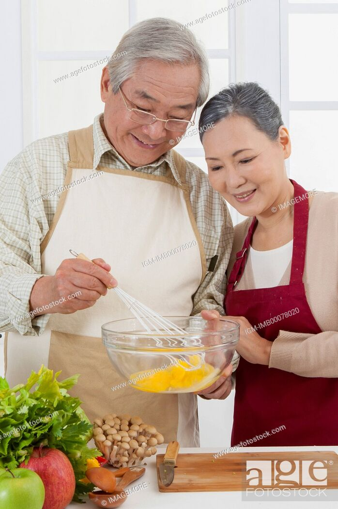 Imagen: Senior couple standing in the kitchen and smiling happily,.