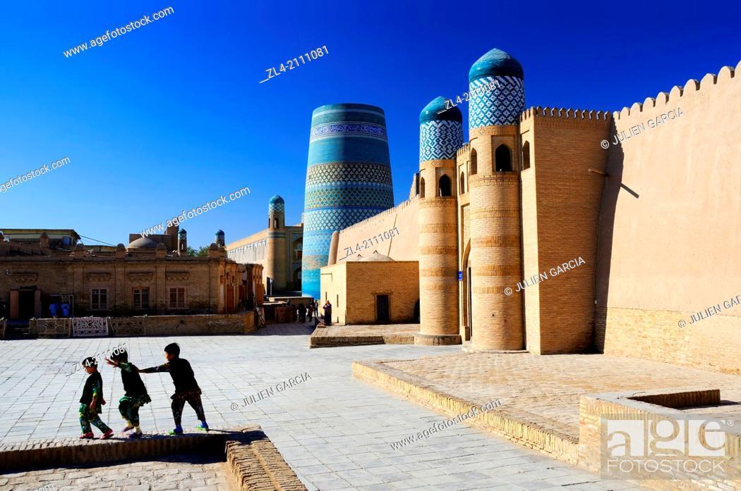 Stock Photo: Children playing near the Kuhna Ark fortress and the unfinished minaret Kalta Minor. Uzbekistan, Khorezm, Khiva, Itchan Kala (inner town).