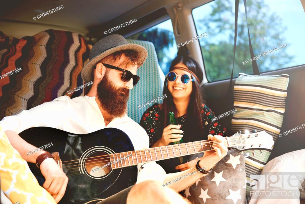 Stock Photo: Young boho couple playing acoustic guitar in recreational van.