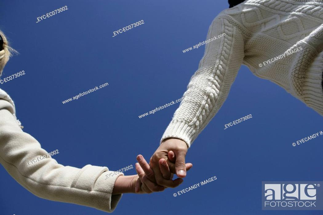Stock Photo: Low angle view of couple holding hands.