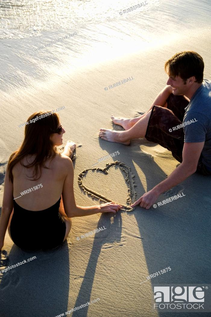 Imagen: Couple on beach drawing valentines in sand.