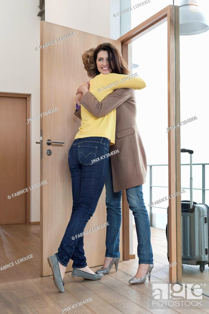 Stock Photo: Woman welcoming her friend at doorway.
