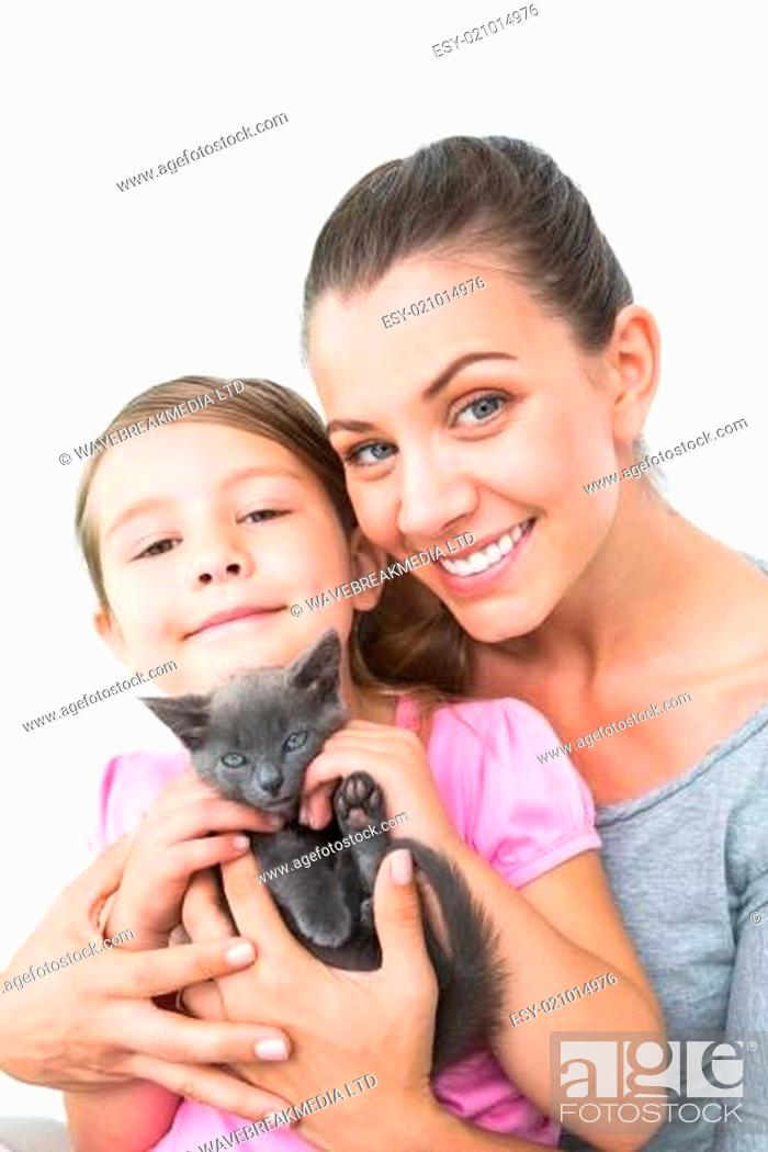 Stock Photo: Smiling mother and daughter sitting with pet kitten together.