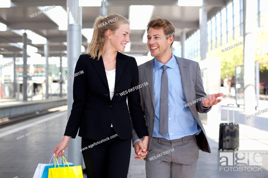 Stock Photo: Germany, North Rhine Westphalia, Duesseldorf, Couple with shopping bags in station, smiling.