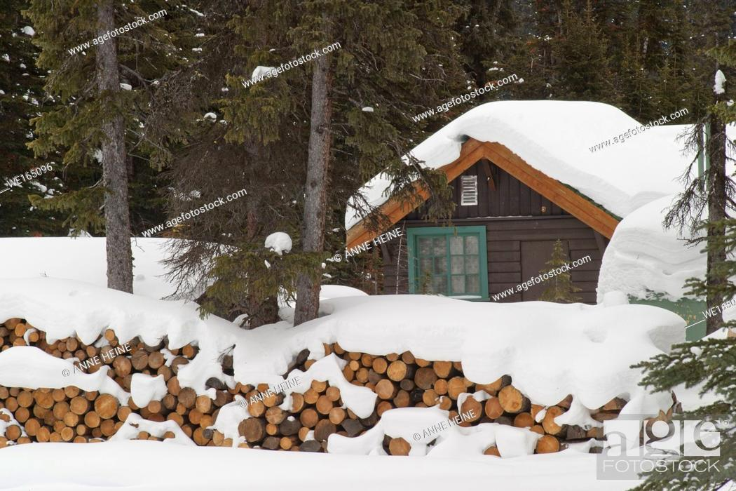 Stock Photo: Cabin in the Rocky Mountains covered in snow with stakes of firewood. Along the shores of Lake O`Hara, Yoho National Park, British Columbia, Canada.