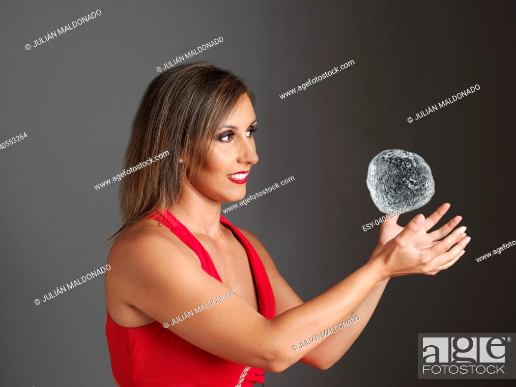 Stock Photo: Young woman trying to catch a water sphere.