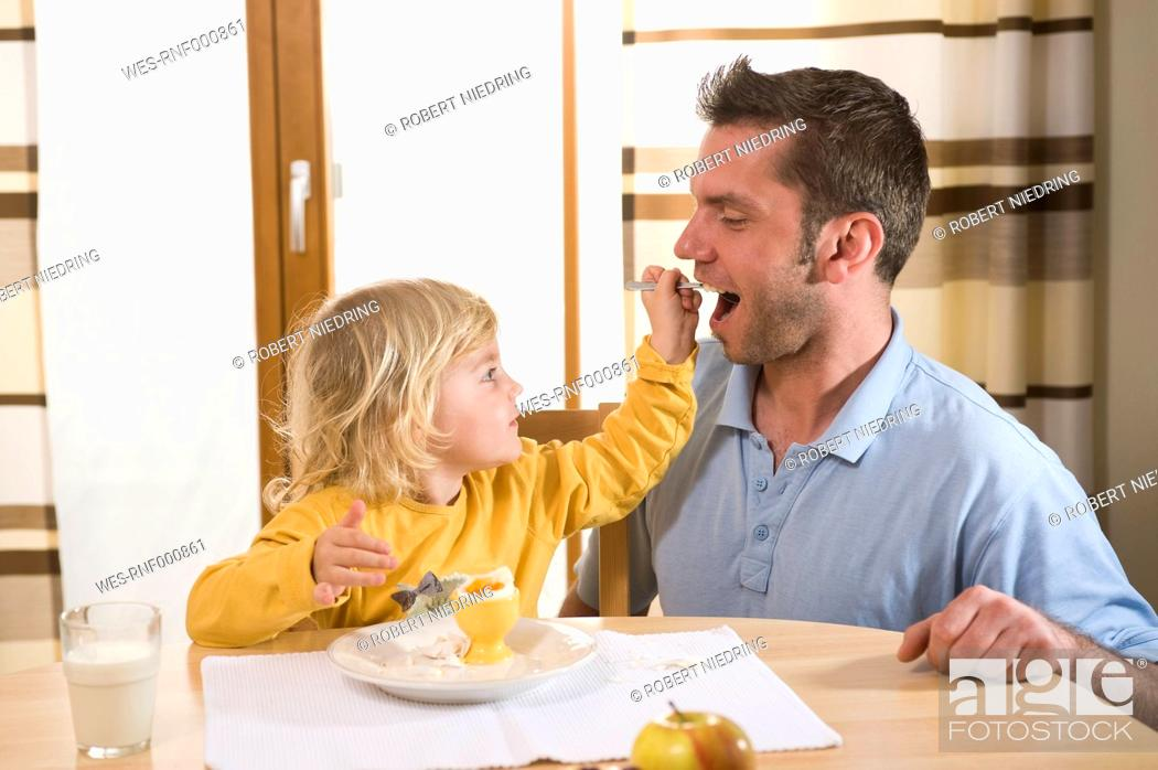 Stock Photo: Daughter feeding boiled egg to father.