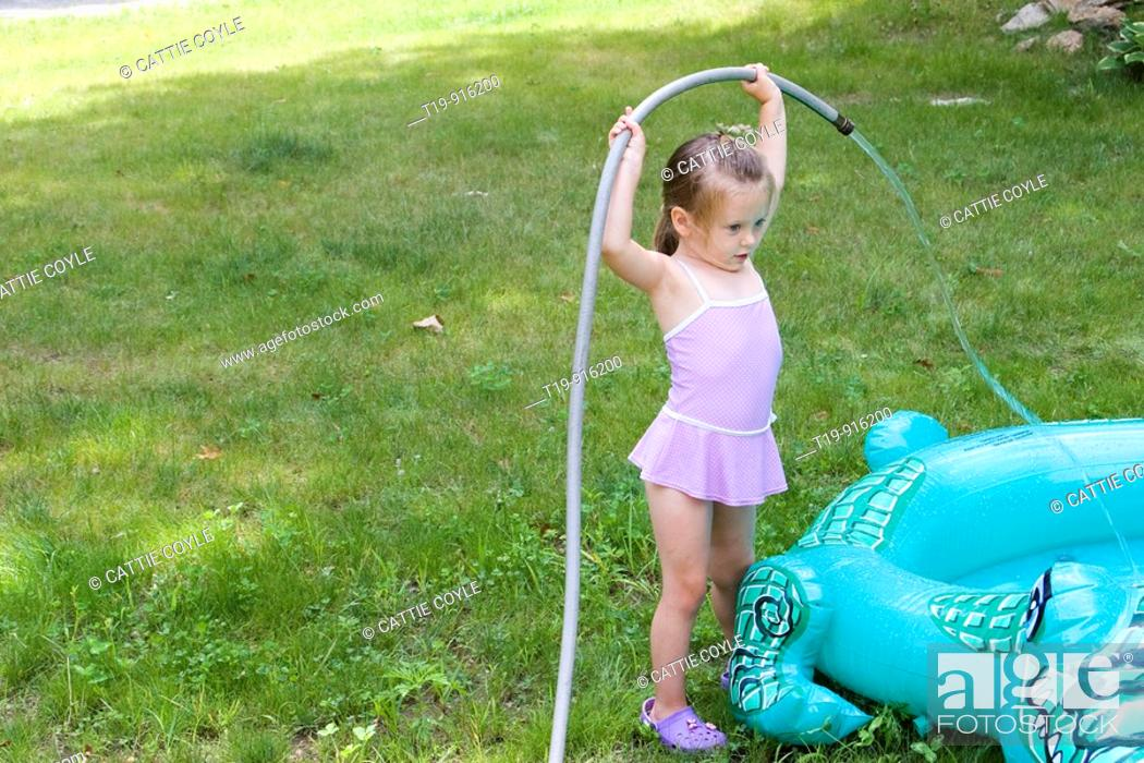 Stock Photo: 4-year old girl filling her inflatable pool with water  MR.