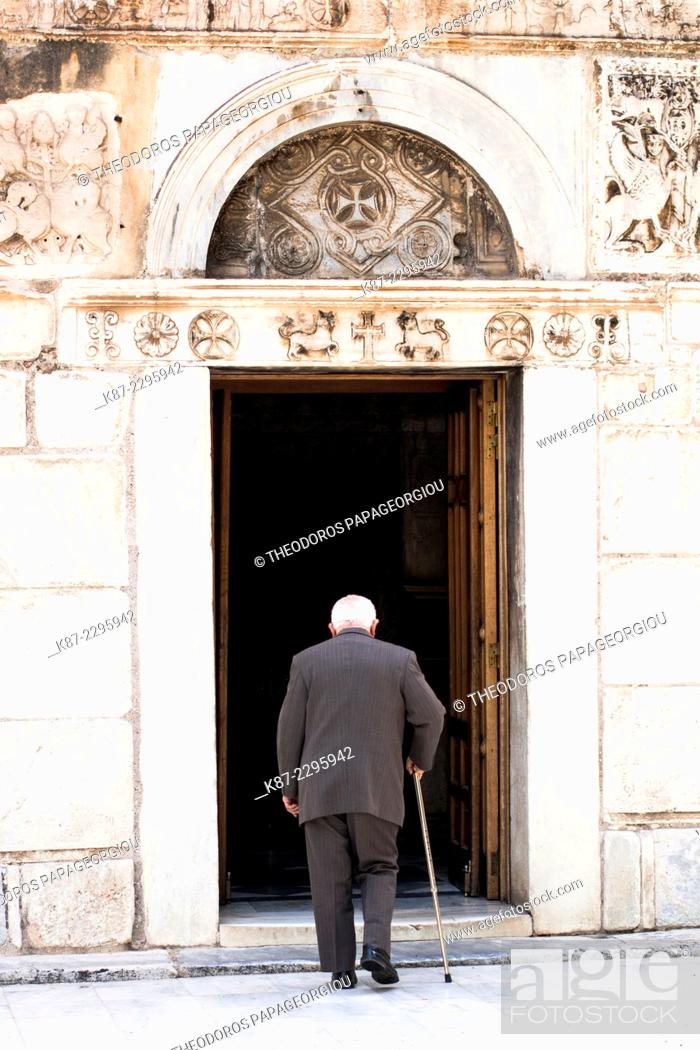 Stock Photo: An old man enters the door of the byzantine church of Agios Eleutherios built in 11th century AD. Athens, Greece.