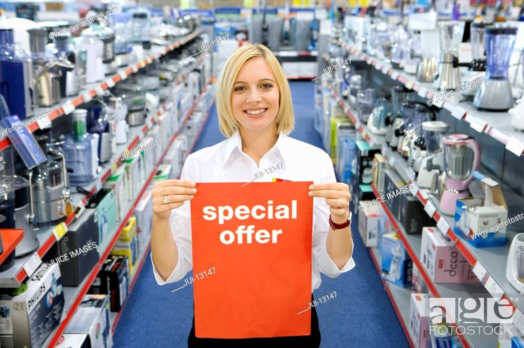 Stock Photo: Young woman in electronics aisle holding 'special offer' sign, smiling, porttrait.
