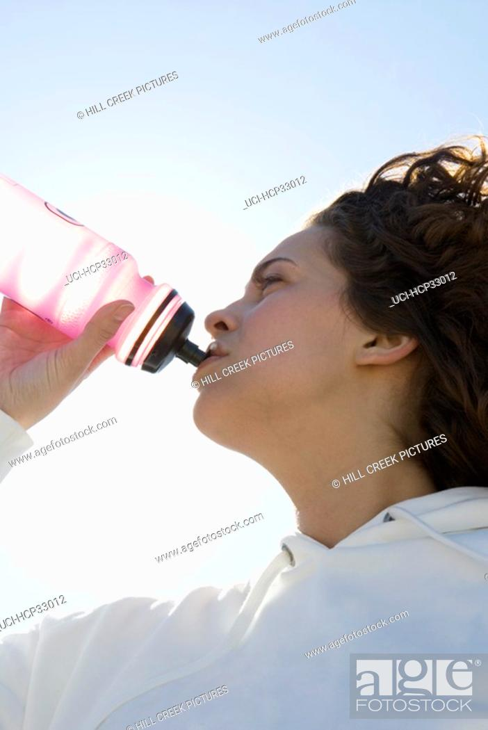Stock Photo: Woman drinking out of water bottle.