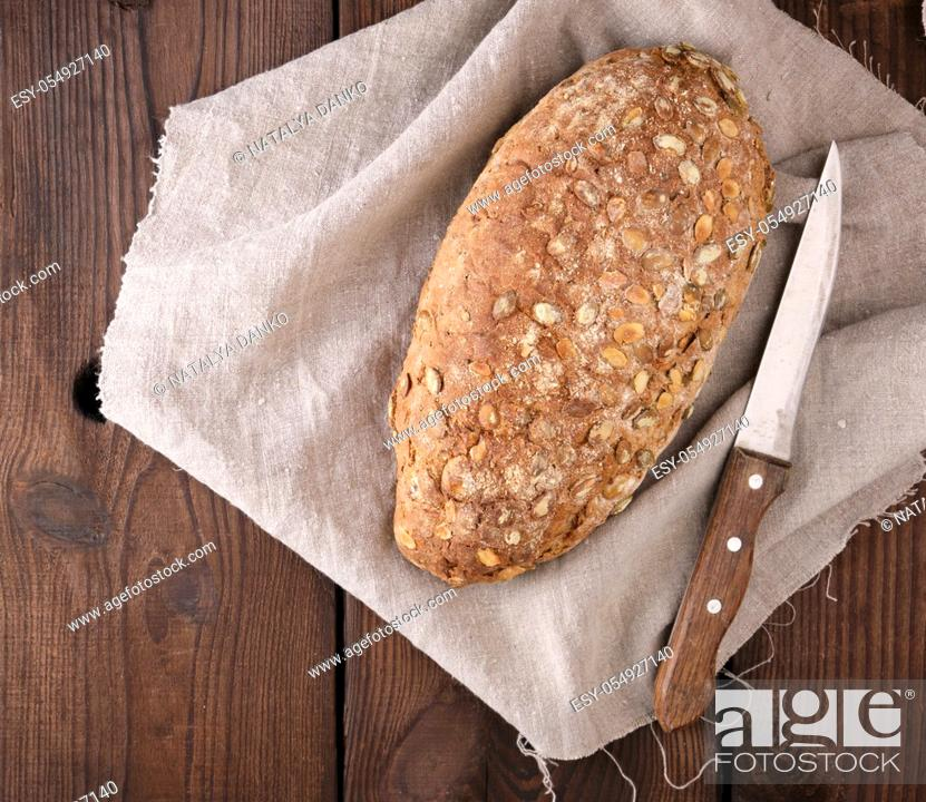 Stock Photo: baked oval bread made from rye flour with pumpkin seeds on a gray linen napkin, top view.
