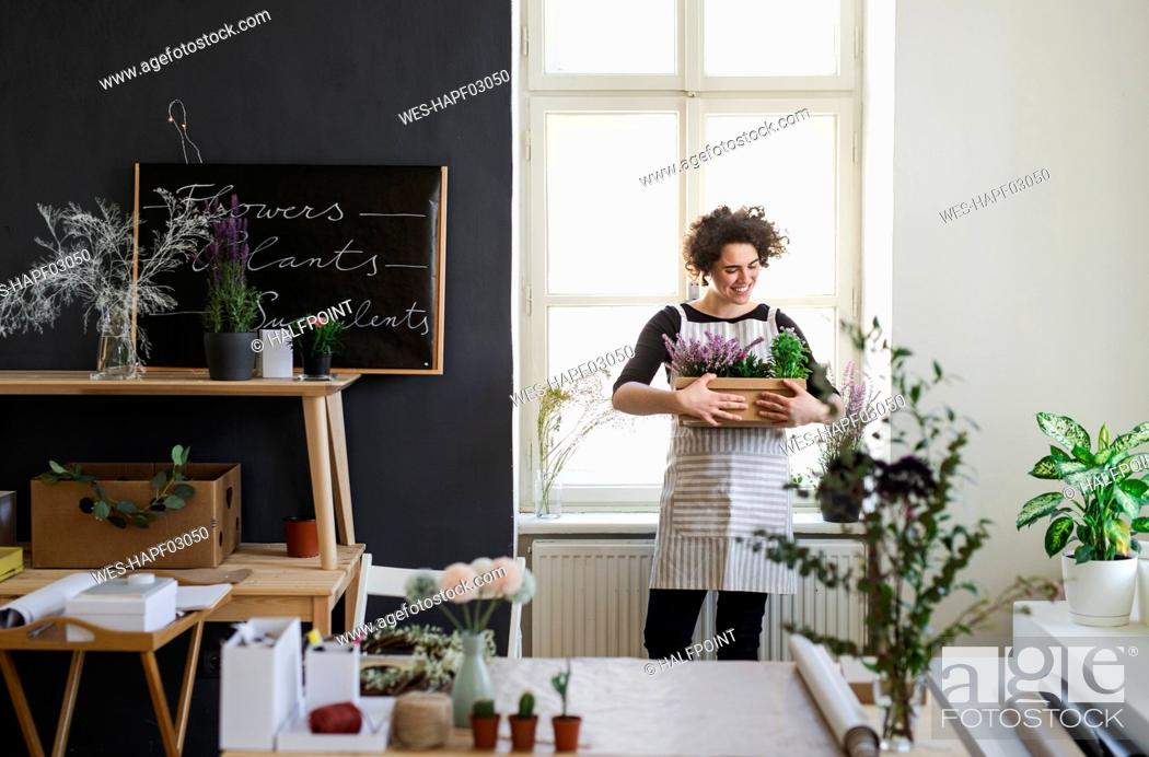 Stock Photo: Smiling young woman holding flowers in a cardboard box in a small shop.