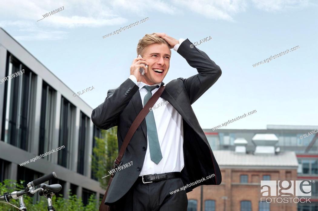 Stock Photo: Happy young businessman using phone, Munich, Bavaria, Germany.