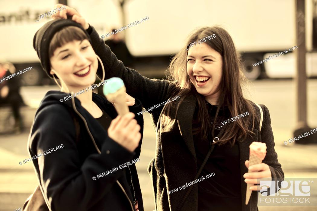 Stock Photo: two vibrant friends with ice cream cones during warm winter day, in city Cottbus, Brandenburg, Germany.