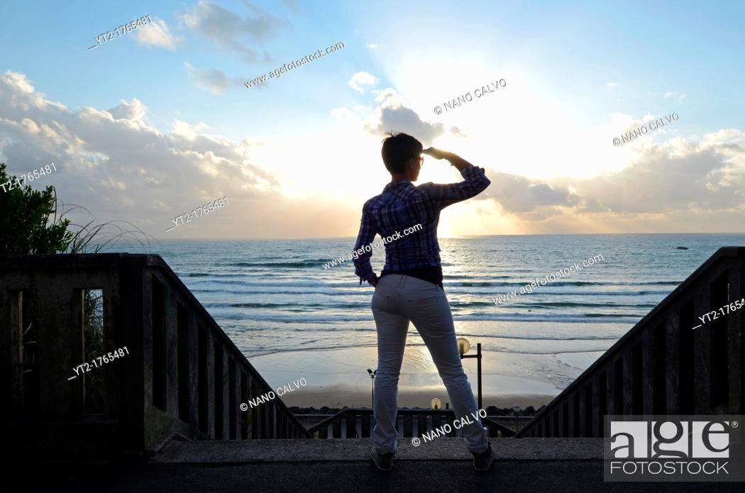 Stock Photo: Young woman at sunset in Cote des Basques, Biarritz.