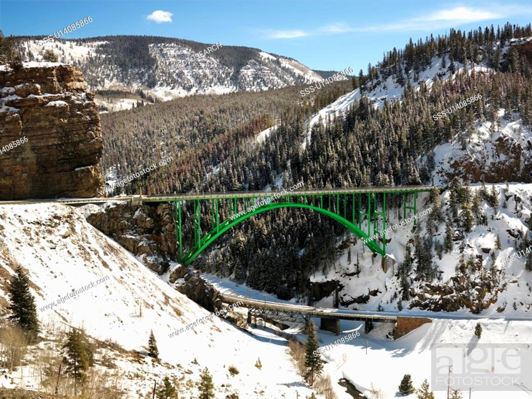 Stock Photo: Mountain landscape with bridge crossing over roadway.