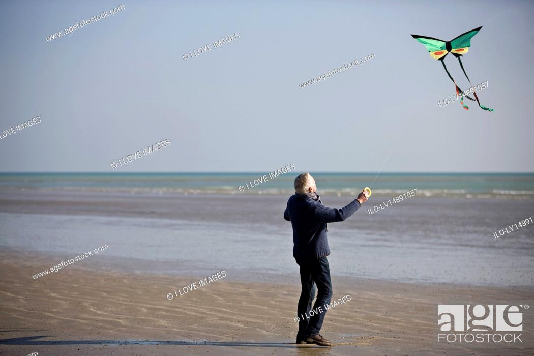 Stock Photo: A senior man flying a kite on the beach.