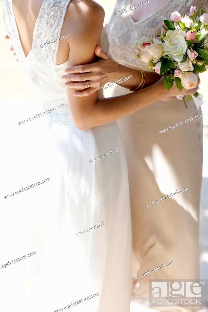 Stock Photo: Mother hugging bride on wedding day.