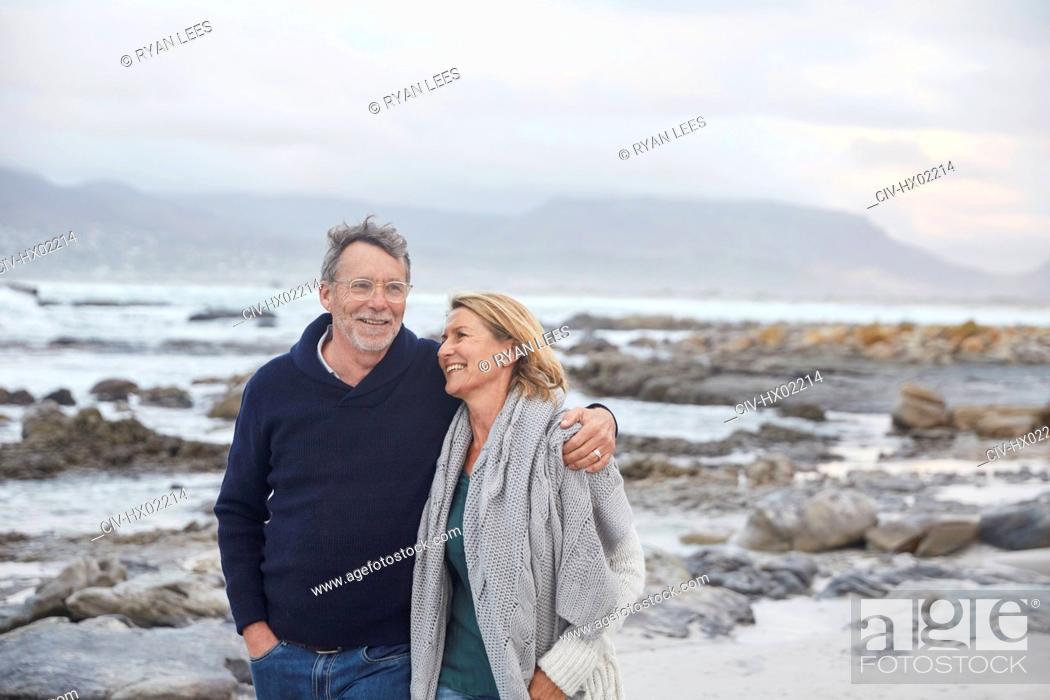 Stock Photo: Smiling senior couple walking on winter beach.