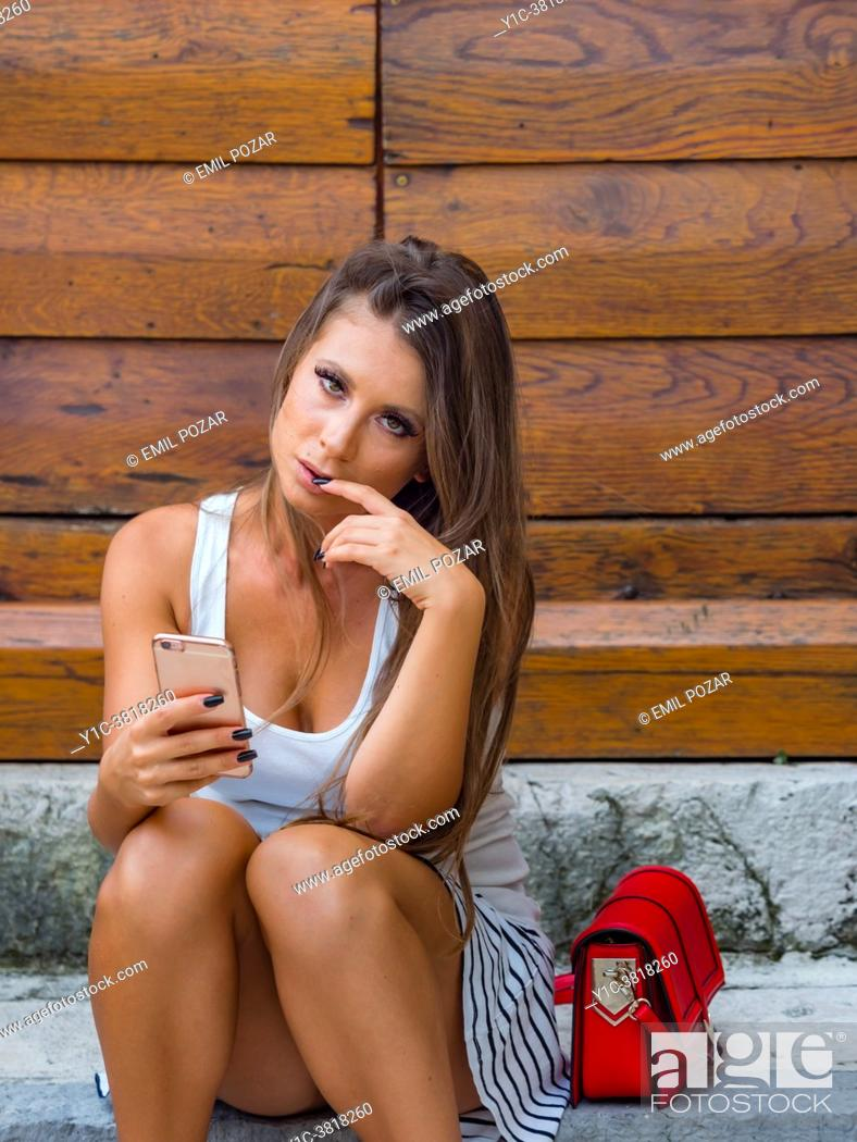 Stock Photo: Young woman concerned worried finger in mouth.