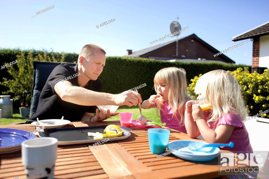 Stock Photo: Father putting food in plate for daughters in back yard on sunny day.