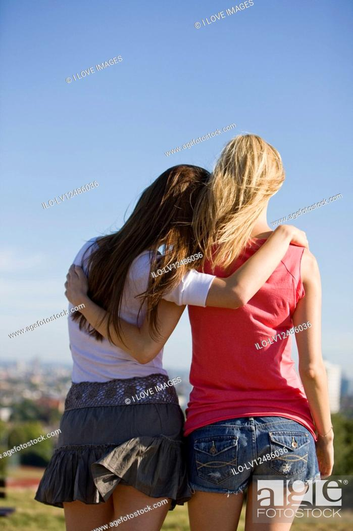Stock Photo: Two young women looking across the city, rear view.