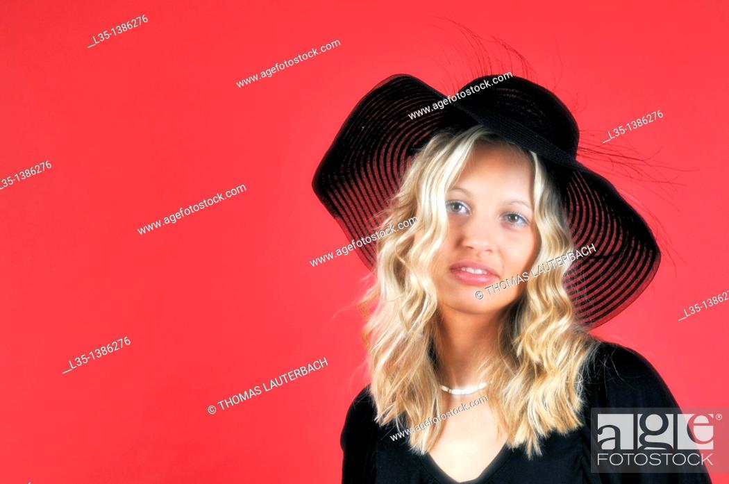 Stock Photo: Young blonde woman in a black hat against a red background.